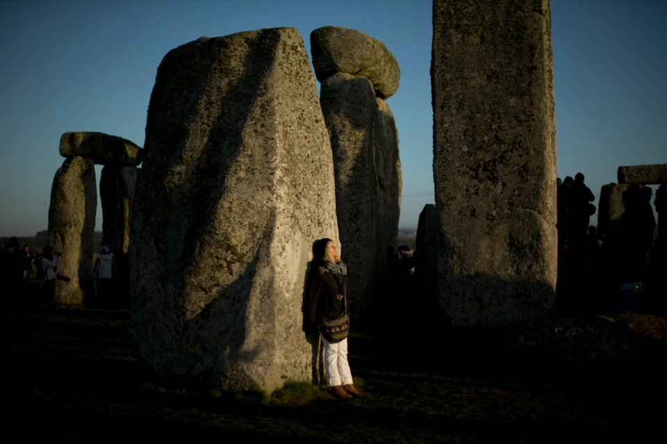 A woman soaks up the sun after its rise at the ancient stone circle of Stonehenge, in southern England, as access to the site is given to druids, New Age followers and members of the public on the annual Winter Solstice, Friday, Dec. 21, 2012. (AP Photo/Matt Dunham)