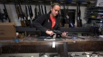 Atlas Tactical co-owner/operator Brooke Stallings handles an assault rifle that is for sale in her shop near Newport, Va. on Dec. 18 2012. (AP Photo/The Roanoke Times/Matt Gentry)
