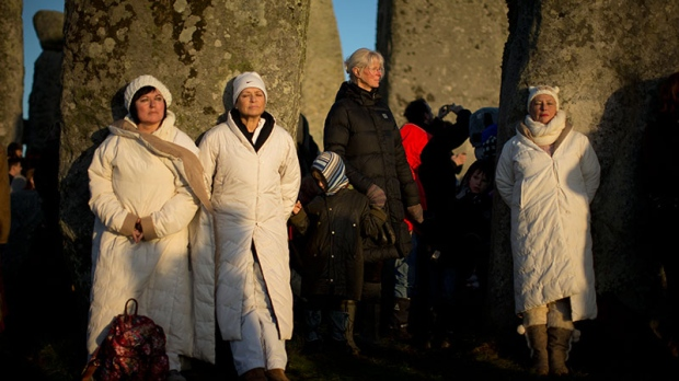 Women soak up the sun after its rise at the ancient stone circle of Stonehenge, in southern England, as access to the site is given to druids, New Age followers and members of the public on the annual Winter Solstice, Friday, Dec. 21, 2012. (AP / Matt Dunham)