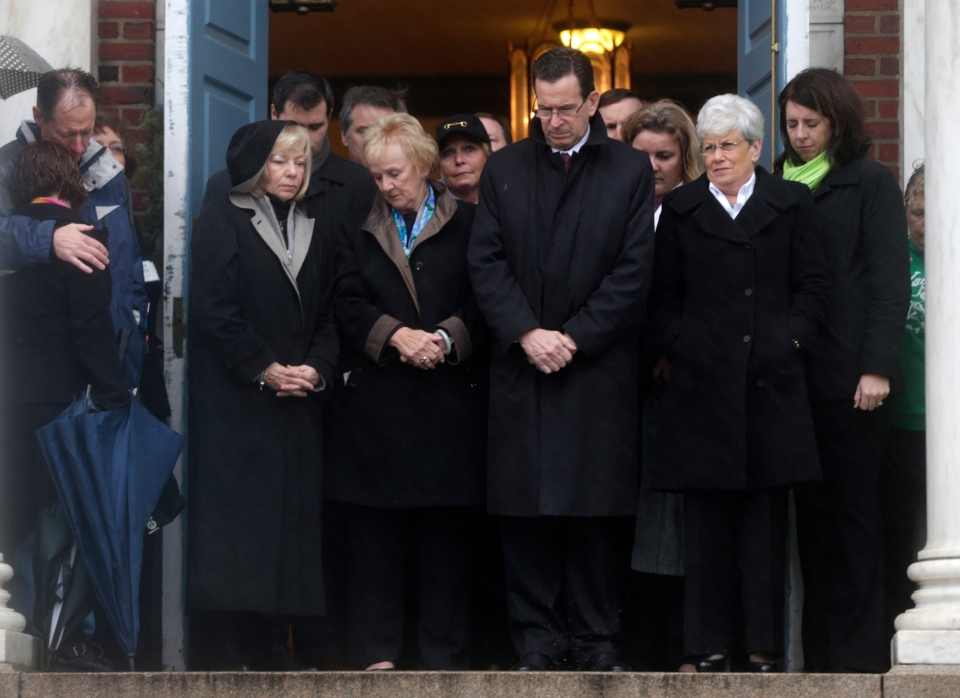 Connecticut Gov. Dan Malloy, center, stands with other officials to observe a moment of silence while bells ring 26 times in Newtown, Conn., Friday, Dec. 21, 2012, in honor of the victims who were killed last Friday during the shooting at Sandy Hook Elementary School. (AP  Seth Wenig)