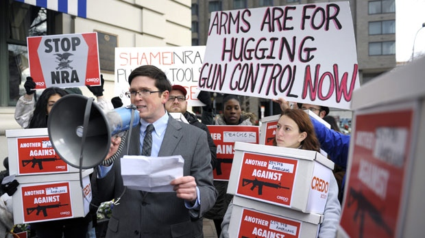 Josh Nelson, campaign manager, CREDO Mobile, centre, speaks after his group was denied entrance to the Williard InterContinental Hotel where they wanted to deliver a petition to the National Rifle Association calling for the NRA to get out of the way of gun control, as the NRA is having a news conference in Washington, Friday, Dec. 21, 2012. (AP / Cliff Owen)