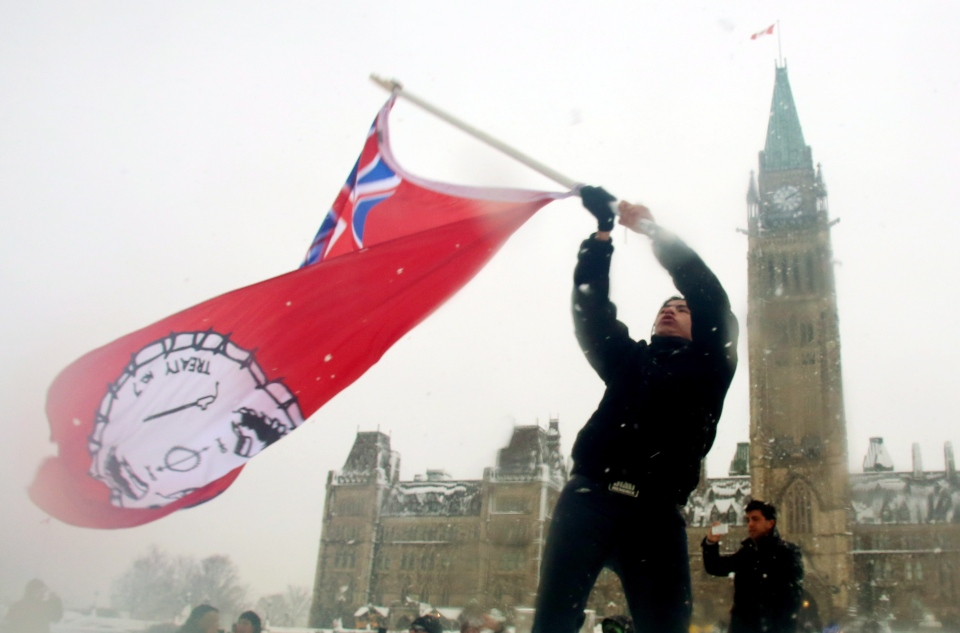 A First Nations member waves a flag as he takes part in a protest on Parliament Hill in Ottawa on Friday, Dec. 21, 2012. (Fred Chartrand / THE CANADIAN PRESS)