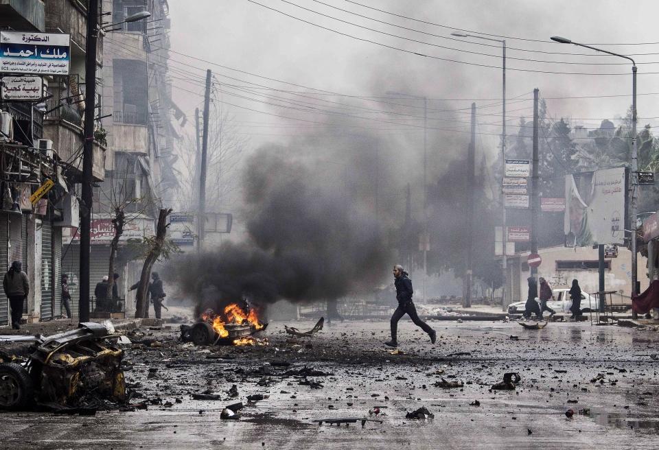 A man runs between debris after a mortar shell hit a street killing several people in the Bustan Al-Qasr district of Aleppo, Syria on Monday, Dec. 17, 2012. (AP / Narciso Contreras)