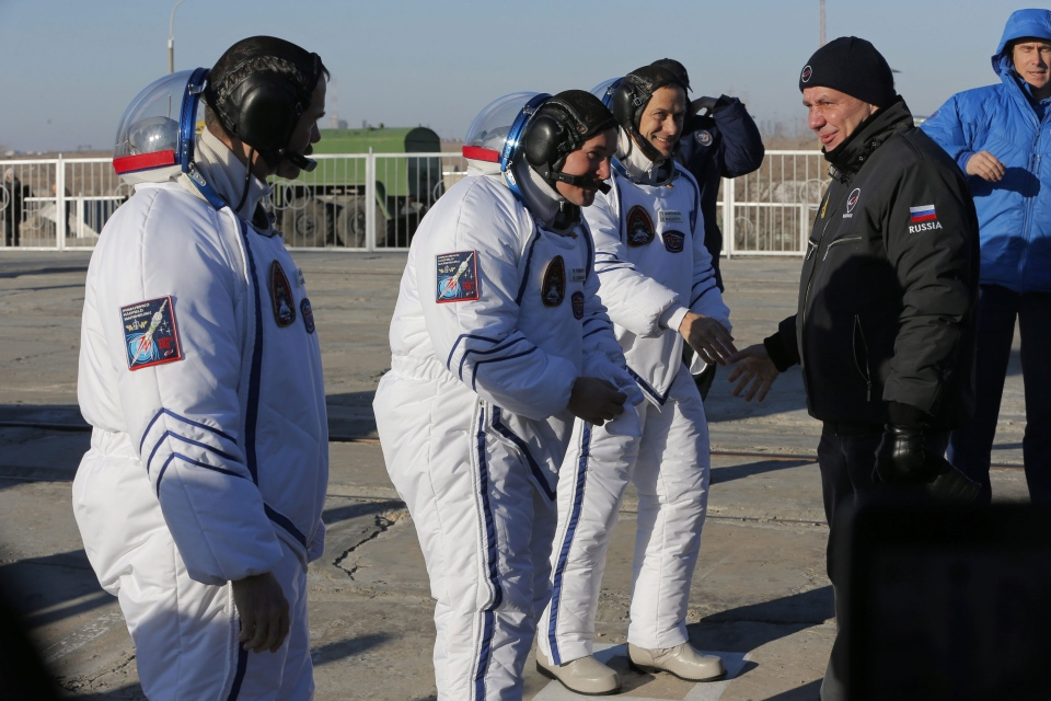 Russia's Space Agency Chief Vladimir Popovkin greets U.S. astronaut Thomas Marshburn, right, Russian cosmonaut Roman Romanenko, center, and Canadian astronaut Chris Hadfield, crew members of the mission to the International Space Station, ISS, prior the launch of Soyuz-FG rocket at the Russian leased Baikonur cosmodrome, Kazakhstan, Wednesday, Dec. 19, 2012. (AP / Dmitry Lovetsky)