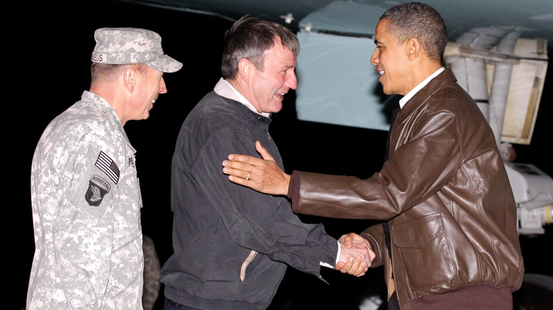 U.S. President Barack Obama is greeted by NATO Commander in Afghanistan Gen. David Petraeus, left, and U.S. Ambassador to Afghanistan Karl W. Elkenberry, center, after stepping off Air Force One during an unannounced visit to Bagram Air Base in Afghanistan. Friday, Dec. 3, 2010. (AP / Pablo Martinez Monsivais)