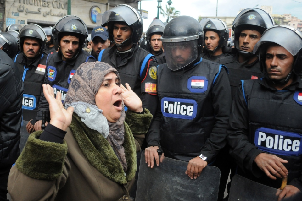 A woman reacts as she stands before riot policemen separating opponents of Egyptian President Mohammed Morsi clashing with Islamist supporters of the president in Alexandria, Egypt, Friday, Dec. 21, 2012. (AP Photo)