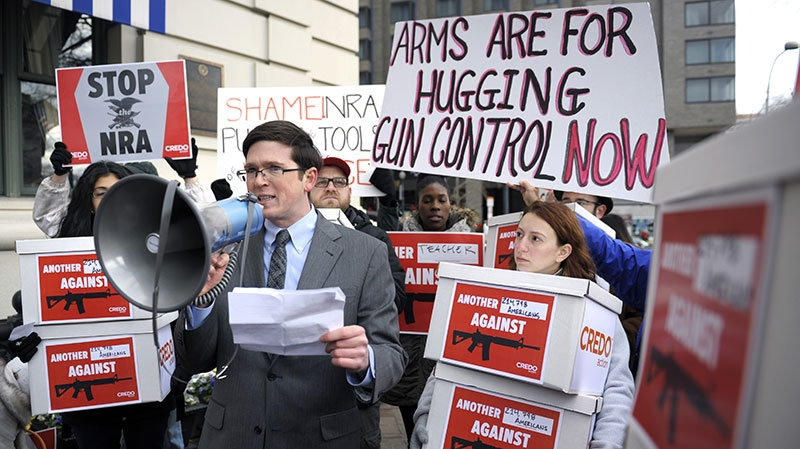 Josh Nelson, campaign manager, CREDO Mobile, speaks after his group was denied entrance to the Williard InterContinental Hotel where they wanted to deliver a petition to the National Rifle Association in Washington, Friday, Dec. 21, 2012. (AP / Cliff Owen)