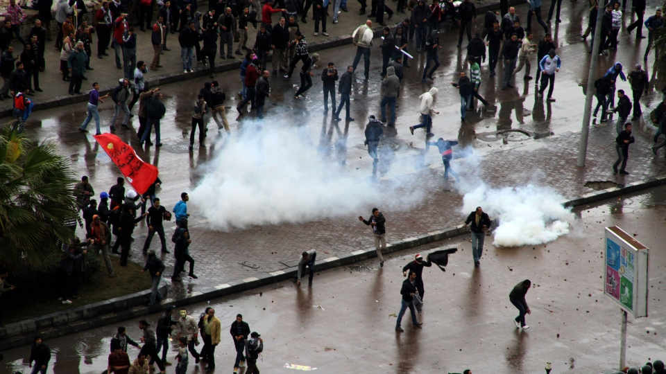 Opponents of Egyptian President Mohammed Morsi clash with Islamist supporters of the president, unseen, as a cordon of riot police separates the groups in Alexandria, Egypt, Friday, Dec. 21, 2012. (AP / Ahmed Ramadan)