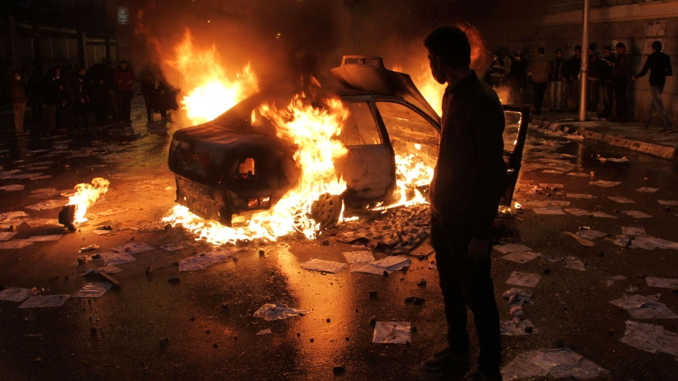 A masked protester watches a vehicle burn during clashes between opponents of Egyptian President Mohammed Morsi and his Islamist supporters in Alexandria, Egypt, Friday, Dec. 21, 2012. (AP Photo)