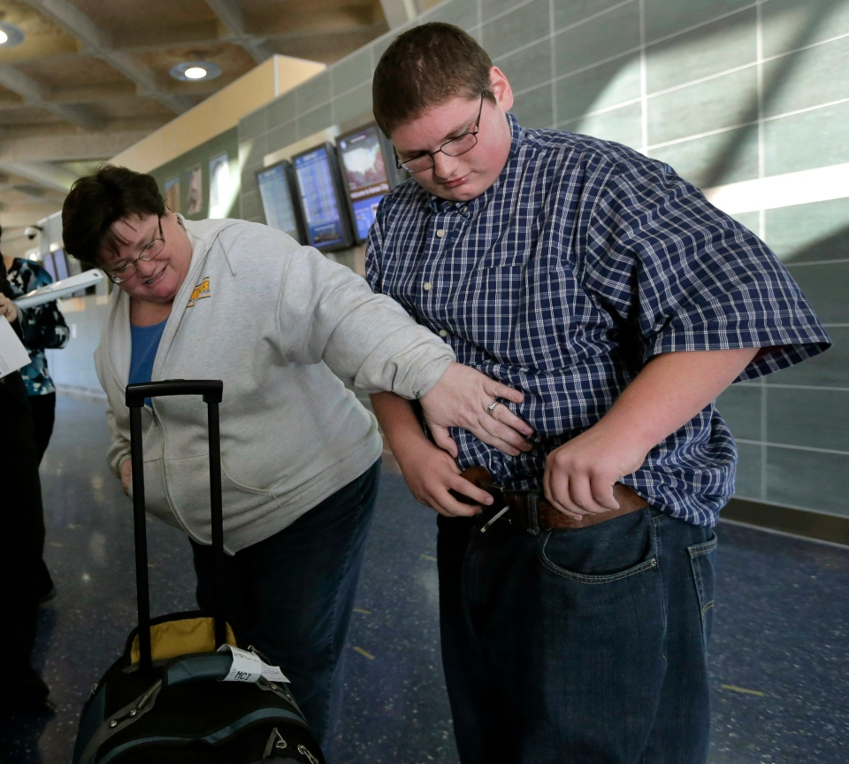 Debbie Alexander checks out her son Jason's baggy-fitting jeans after he returned from a four-month stay at a weight-loss boarding school, at the Kansas City International Airport in Kansas City, Mo., Friday, Dec. 21, 2012. (AP / Charlie Riedel)