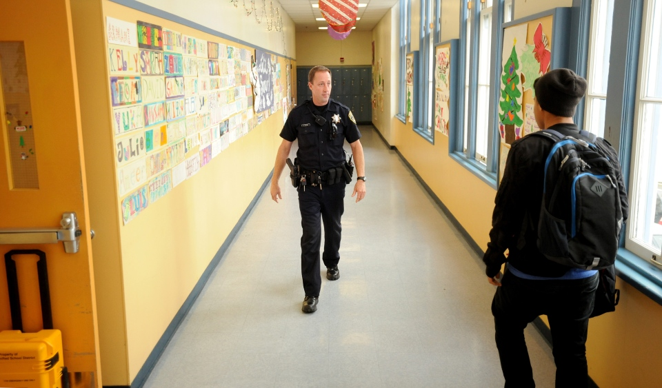 Officer Rick Moore of the Oakland school district police patrols Oakland Technical High School in Oakland, Calif, on Dec. 17, 2012. (AP / Noah Berger)