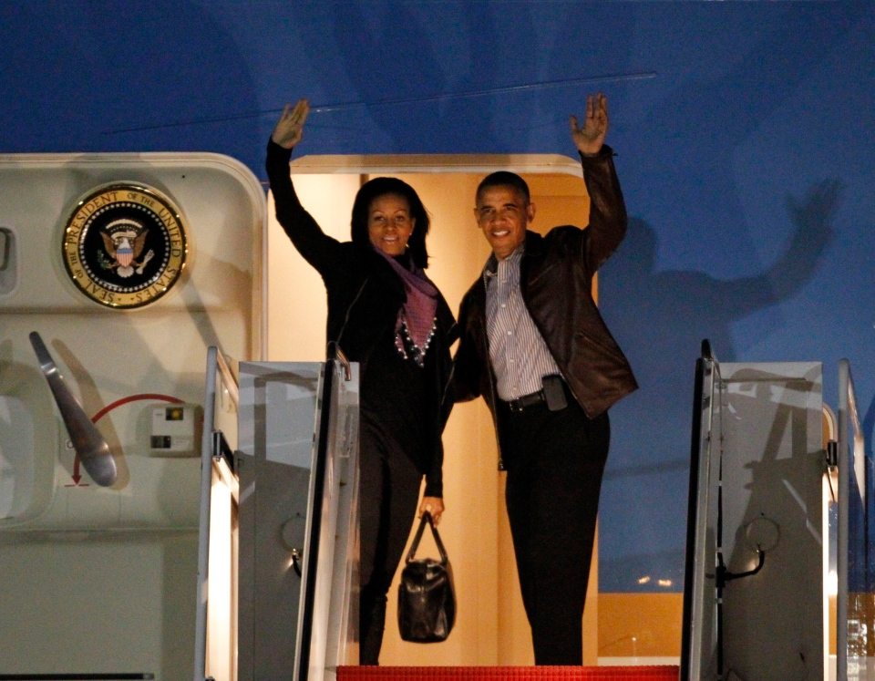 U.S. President Barack Obama and first lady Michelle Obama wave as they board Air Force One at Andrews Air Force Base, Md., Friday, Dec. 21, 2012 before departing for Hawaii. (AP Photo/Ann Heisenfelt)