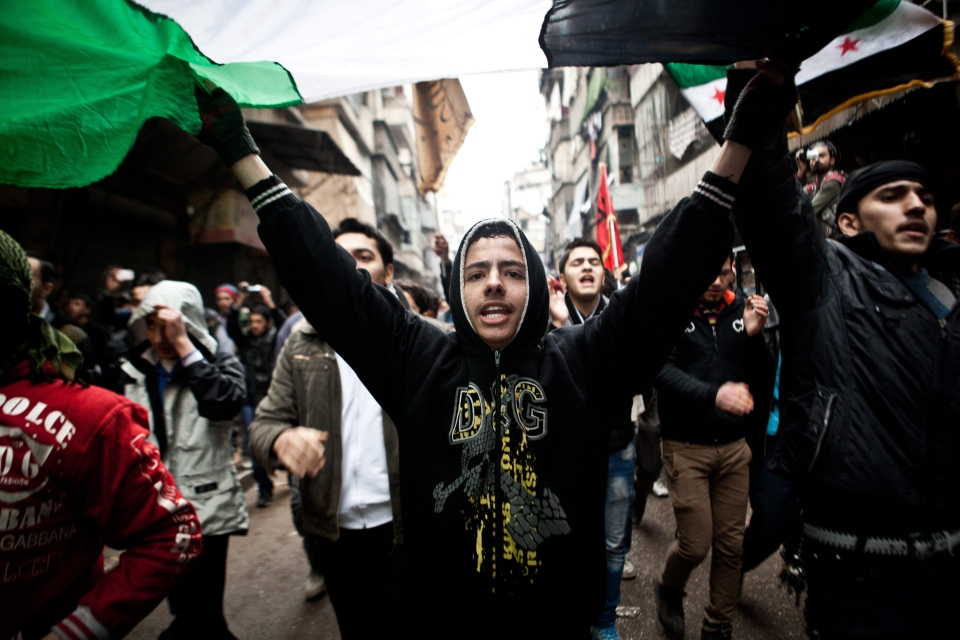 Syrians carry a large revolution flag and chant slogans during a Friday protest in Aleppo, Syria, Friday, Dec. 21, 2012.(AP / Virginie Nguyen Hoang)