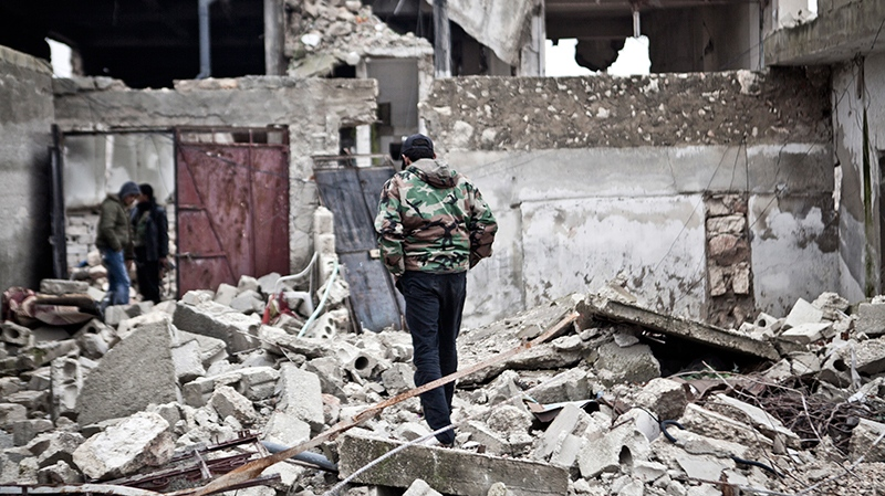 Free Syrian Army fighters walk amid the ruins of a village situated a short distance from an area where fighting between rebels and government forces continues, Saturday, Dec. 22, 2012. (AP/ Virginie Nguyen Hoang)