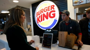 A customer purchases a meal at a Burger King restaurant in Marseille-Provence airport, in Marignane, France, on Saturday, Dec. 22, 2012. (AP Photo/Claude Paris)