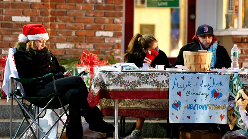 A woman, left, wears a Christmas hat while sitting with a group seeking donations for the victims of the Sandy Hook Elementary School shooting in the Sandy Hook village of Newtown, Conn., the site of a shooting massacre last week, Thursday, Dec. 20, 2012.  (AP / Julio Cortez)