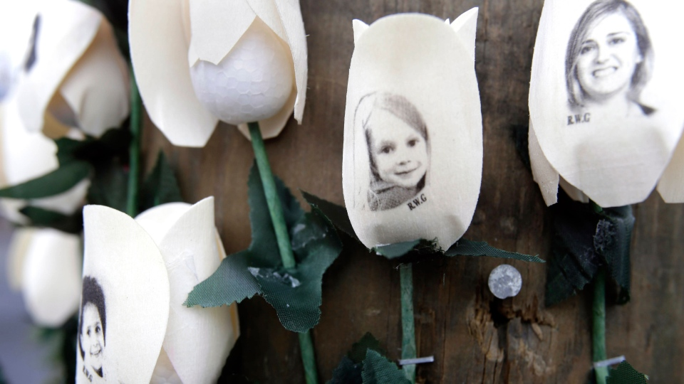 Photos showing those killed in the shootings at Sandy Hook Elementary School are imprinted on fake roses at a memorial in the Sandy Hook village of Newtown, Conn., Saturday, Dec. 22, 2012. (AP / Seth Wenig)