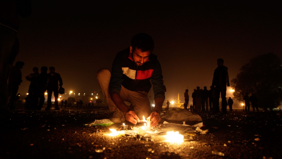 An Indian protester lights a candle near the Presidential Palace in New Delhi, India, Saturday, Dec. 22, 2012. (AP / Altaf Qadri)