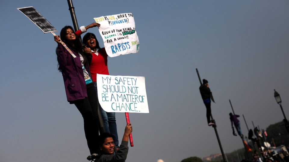 Indian women hold placards as they shout slogans from a flag post near the Presidential Palace during a protest in New Delhi, India, Saturday, Dec. 22, 2012. (AP / Altaf Qadri)