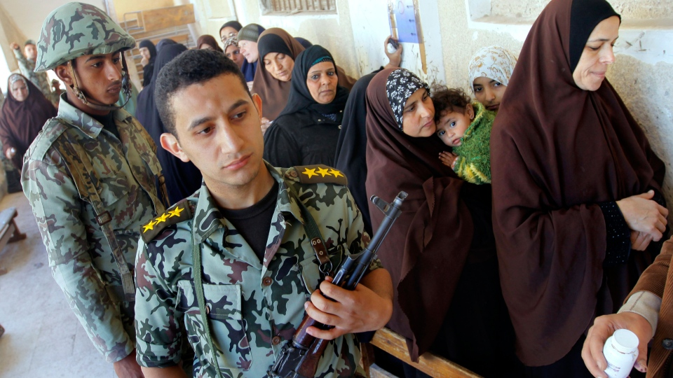 An Egyptian army officer stands near women as they prepare to vote for the second round of a referendum on a disputed constitution drafted by Islamist supporters of President Mohammed Morsi in Giza, Egypt, Saturday, Dec. 22, 2012. (AP / Amr Nabil)