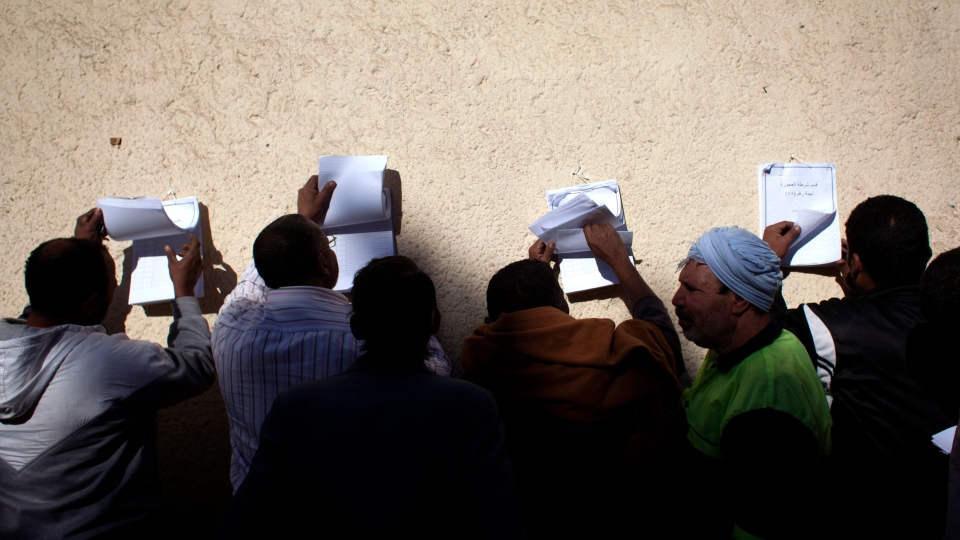 Egyptian voters check voter lists outside a polling station during the second round of a referendum on a disputed constitution drafted by Islamist supporters of president Mohammed Morsi, in Giza, Egypt, Saturday, Dec. 22, 2012. (AP / Nasser Nasser)