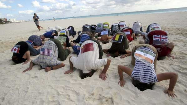 Sierra Club activists wearing flags, representing over 20 countries, take part in a protest by hiding their heads in the sand in the city of Cancun, Mexico Friday Dec. 3, 2010. (AP Photo)