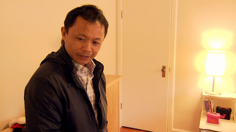 Nilo Tumanda, a widowed father of two, tears up as he looks at the furnished home donated to him by the community. December 22, 2012. (CTV)