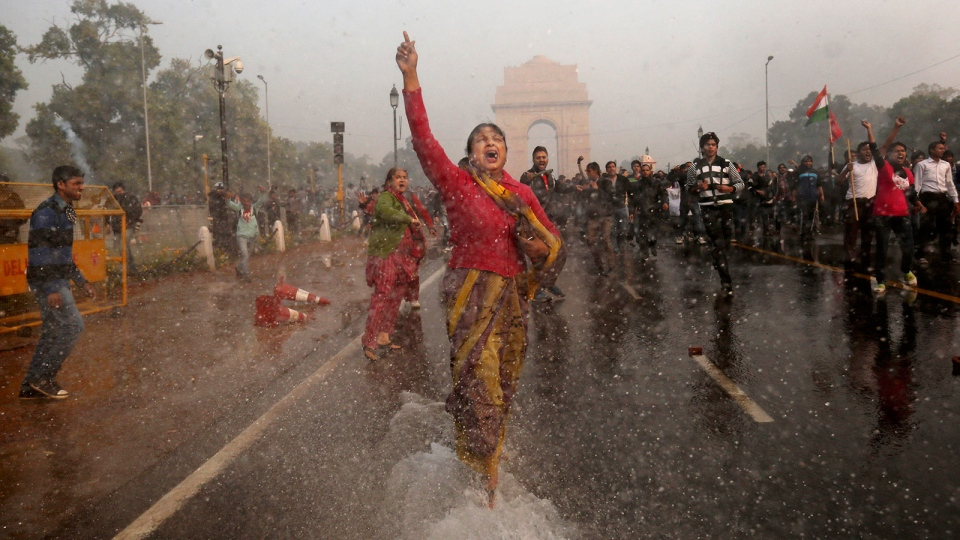A female protester shouts as she is hit with an Indian police water cannon during a violent demonstration near the India Gate against a gang rape and brutal beating of a 23-year-old student on a bus last week, in New Delhi, India, Sunday, Dec. 23, 2012. (AP / Kevin Frayer)