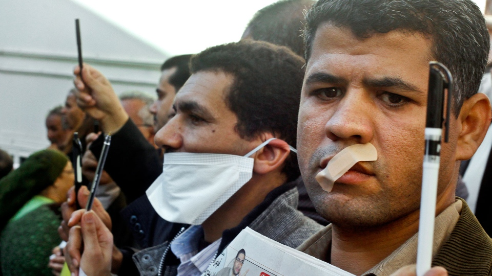 Egyptian journalists tape their mouths and raise their pens during a demonstration against the draft constitution in Cairo, Egypt, Sunday, Dec. 23, 2012. (AP / Amr Nabil)