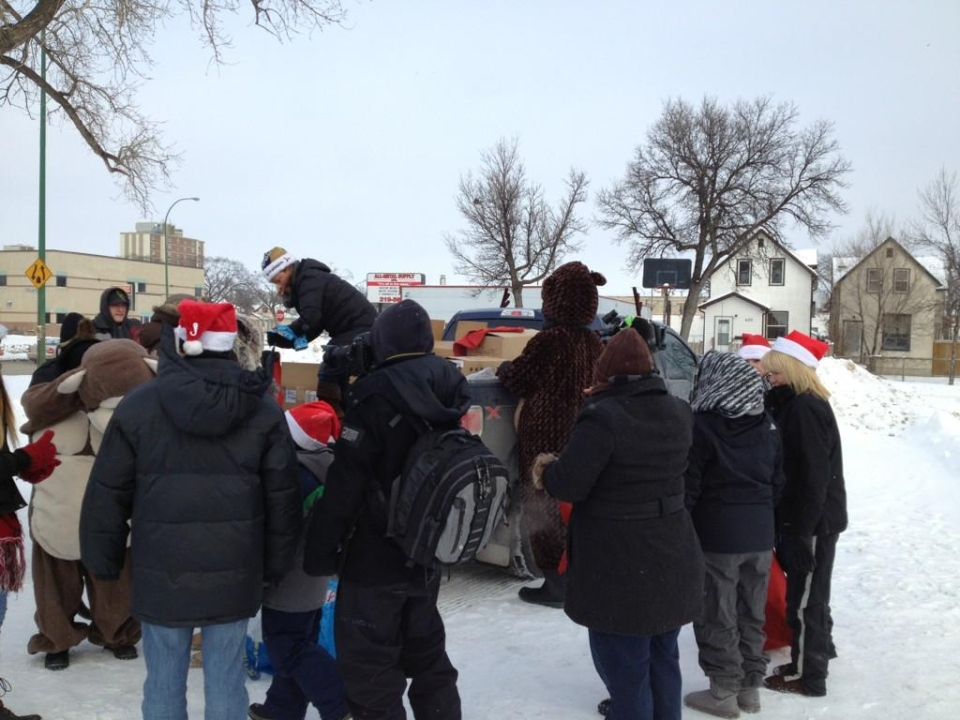 A group of volunteers hand out over 1,000 Christmas presents to strangers in the North End as random acts of kindness.