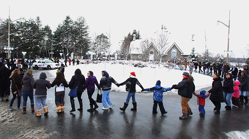 First Nations members block traffic as they form a circle while protesting on the street outside Prime Minister Stephen Harper's official residence at 24 Sussex Drive in Ottawa on Saturday, December 22, 2012. (Fred Chartrand / THE CANADIAN PRESS)