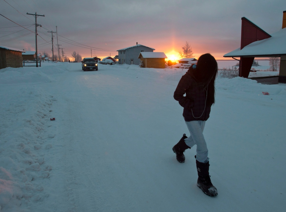 A girl walks along the streets as the sun rises Tuesday, December 18, 2012, on the Fort Hope First Nation, Ont. (THE CANADIAN PRESS/Ryan Remiorz)