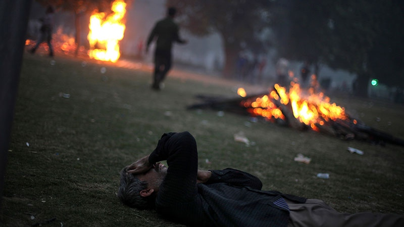 An Indian man overwhelmed by tear smoke lies on the ground during a violent protest in New Delhi, India, Sunday, Dec. 23, 2012. (AP / Altaf Qadri)