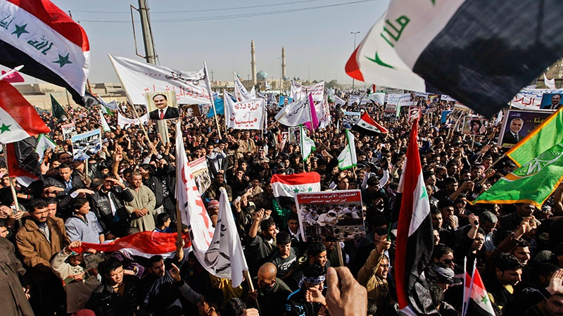 Protesters chant slogans against the Iraq's Shiite-led government as they wave national flags and hold posters of Sunni Finance Minister Rafia al-Issawi during a demonstration in Fallujah, Iraq, Sunday, Dec. 23, 2012. (AP / Khalid Mohammed)