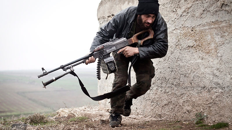 A Free Syrian Army fighter takes cover during fighting with the Syrian Army in Azaz, Syria, Monday, Dec. 17, 2012. (AP / Virginie Nguyen Huang)