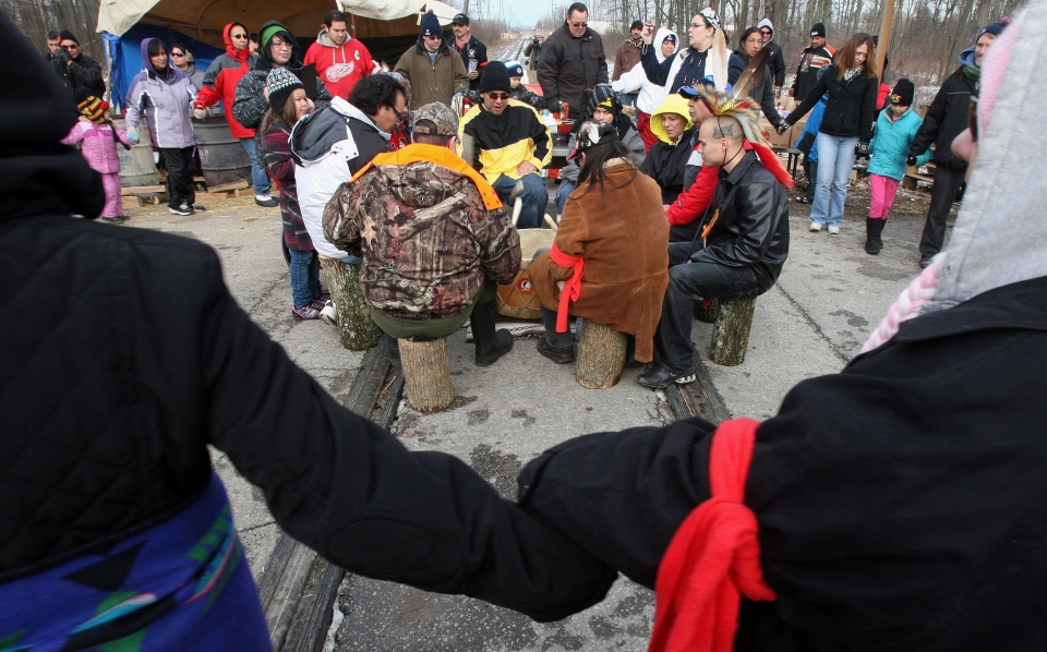 Drummers play on the tracks as people from Aamjiwnaang First Nation and supporters gather for a meeting with officials as their blockade of the CN St. Clair spur line continues in Sarnia, Ont., on Sunday, Dec. 23, 2012. (Dave Chidley / THE CANADIAN PRESS)
