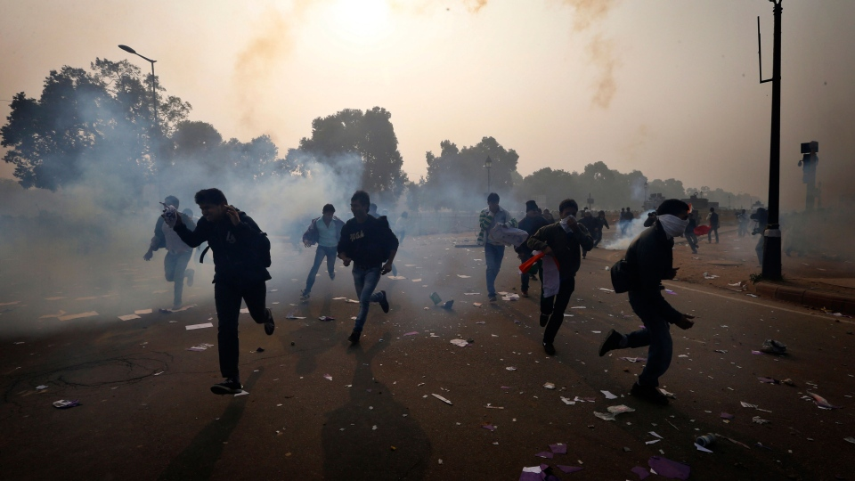 Protestors run as Indian police officers fire tear gas to disperse them near the India Gate as they protest against the gang rape and brutal beating of a 23-year-old student on a bus last week, in New Delhi, India, Sunday, Dec. 23, 2012. (AP / Saurabh Das)