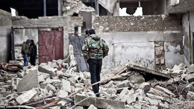 Free Syrian Army fighters walk amid the ruins of a village situated a short distance from an area where fighting between rebels and government forces took place on Saturday, Dec. 22, 2012. (AP / Virginie Nguyen Hoang)