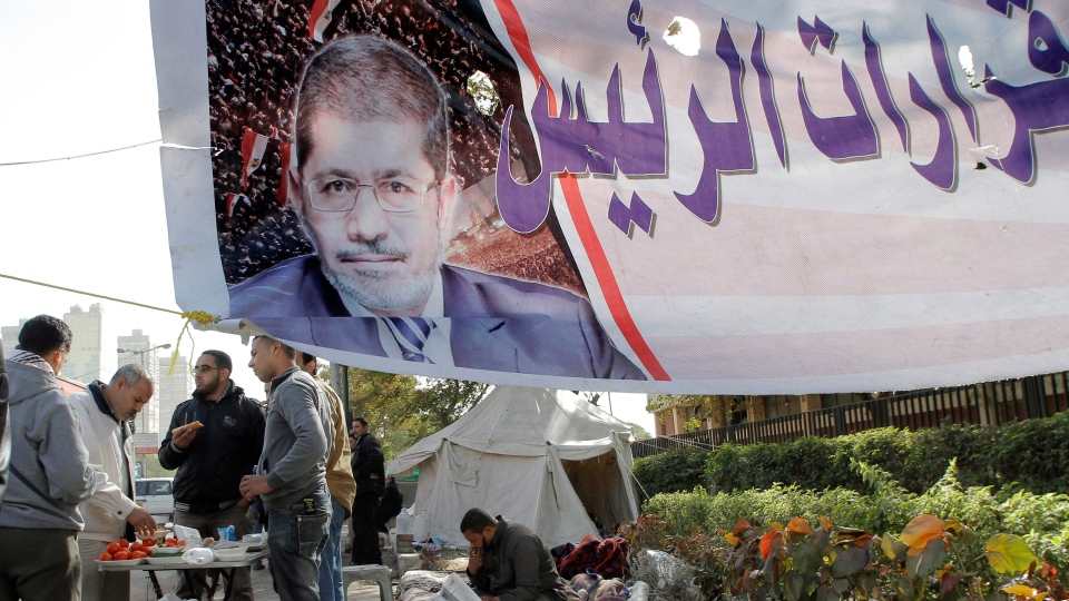 Islamist protesters eat and read newspapers under a banner supporting Egyptian President Mohammed Morsi in front of the Supreme Constitutional Court in Cairo, Egypt, Thursday, Dec.20, 2012. (AP / Amr Nabil)