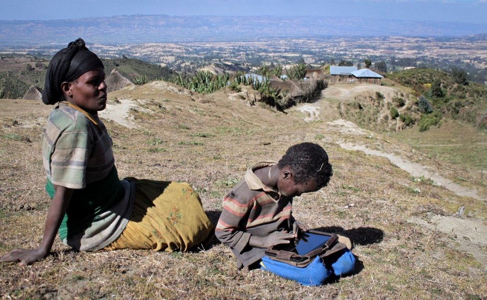 In this photo taken Tuesday, Nov. 27, 2012, Abelbech Wagari sits near her son, Kelbesa Negusse as he plays with a tablet computer given to him by the One Laptop Per Child project in the village of Wenchi, Ethiopia. (AP / Jason Straziuso)