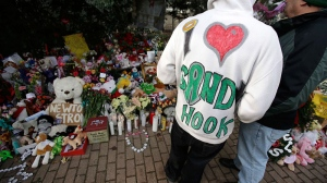 A Sandy Hook resident wears a handmade sweatshirt in support of his town while looking at a memorial to the Newtown shooting victims in the Sandy Hook village of Newtown, Conn., Saturday, Dec. 22, 2012.  (AP / Seth Wenig)