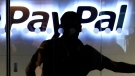 A PayPal employee walks past the PayPal logo at the international headquarters in Singapore, Wednesday, March 17, 2010. (AP / Wong Maye-E)