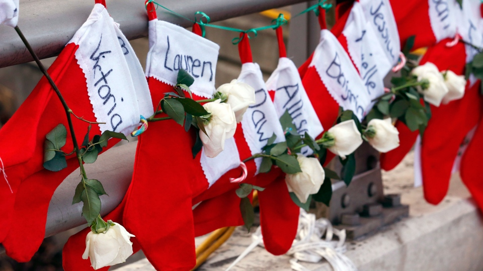 Christmas stockings with the names of shooting victims hang from railing near a makeshift memorial near the town Christmas tree in the Sandy Hook village of Newtown, Conn. Wednesday, Dec. 19, 2012. (AP /Julio Cortez)