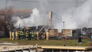 Firefighters gather around a burning house after they were let back into the area to battle the blaze, Monday Dec. 24, 2012, in Webster, N.Y.  (AP / Democrat & Chronicle, Jamie Germano)