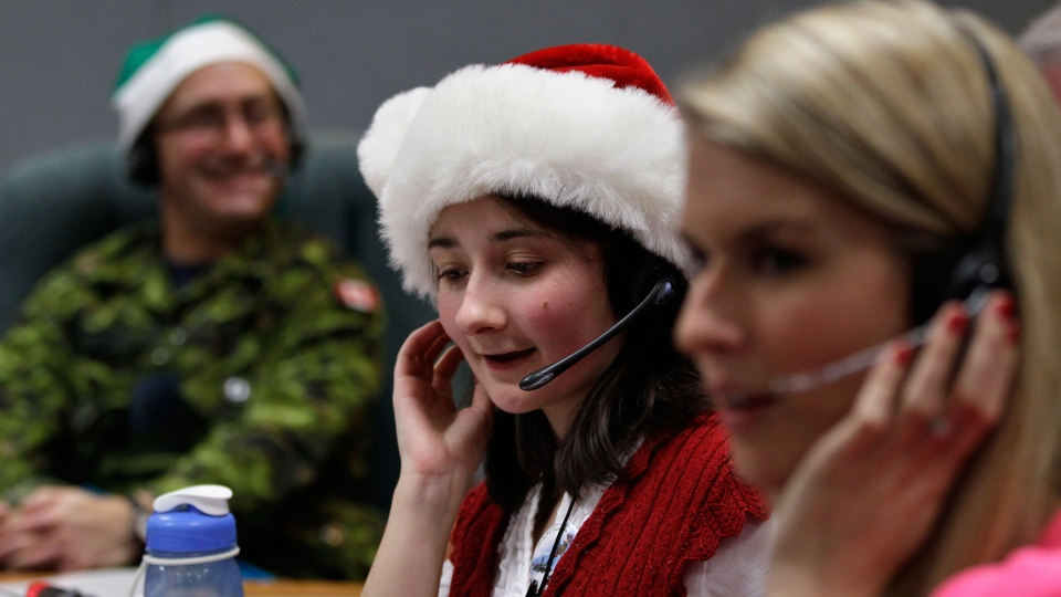 Volunteer Katherine Beaupre takes phone calls from children asking where Santa is and when he will deliver presents to their house, during the annual NORAD Tracks Santa Operation, at the North American Aerospace Defense Command, or NORAD, at Peterson Air Force Base, in Colorado Springs, Colo., Monday Dec. 24, 2012. (AP / Brennan Linsley)