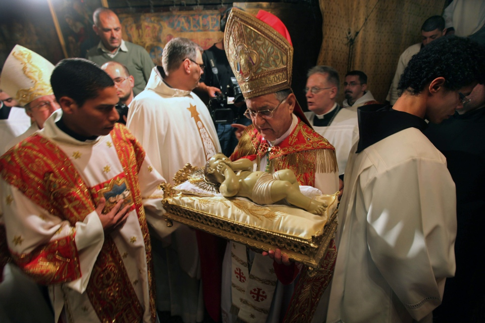 Latin Patriarch of Jerusalem Fouad Twal, centre, holds the Baby Jesus as he and clergy arrive to pray at the Grotto, traditionally believed by Christians to be the birthplace of Jesus Christ, at the Church of the Nativity, in the West Bank town of Bethlehem, early Tuesday, Dec. 25, 2012. (AP / Abed Al Hashlamoun, Pool)