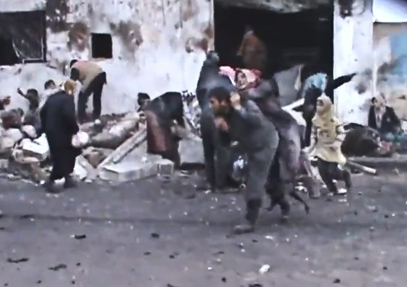This image shows a Syrian man carrying an elderly woman after a government airstrike hit the Hama Suburb of Halfaya, Syria on Sunday, Dec. 23, 2012.  (AP / Shaam News Network via AP video)