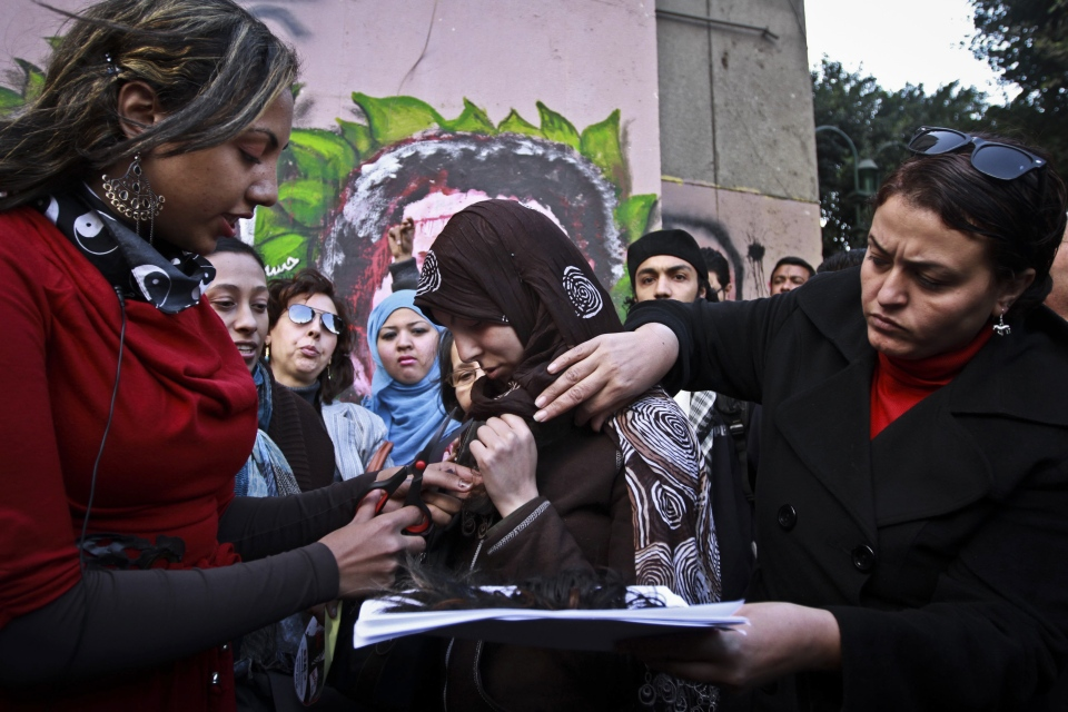 An Egyptian woman cuts the hair of a veiled woman during a demonstration in Tahrir Square, Cairo, Egypt on Tuesday, Dec. 25, 2012. Women cut their hair to protest against the Islamist-oriented constitution on Tuesday. (AP / Ahmed Abd El Latef, El Shorouk)