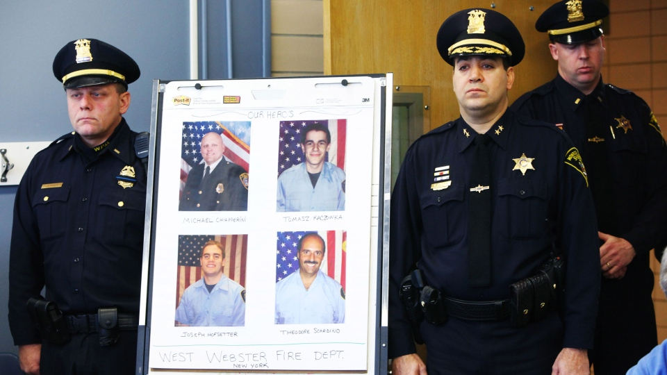 Monroe County Sheriff Deputy Chief Steve Scott, second from right, and Webster Police Lt. Joseph Rieger stand by the photo of the dead and injured firefighters during a news conference in Webster, N.Y., Tuesday, Dec. 25, 2012. (AP / Democrat & Chronicle, Marie De Jesus)