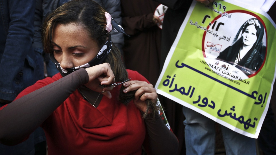 An Egyptian woman cuts her hair during a demonstration in Tahrir Square, Cairo, Egypt, Tuesday, Dec. 25, 2012. Women cut their hair to protest against the Islamist-oriented constitution on Tuesday. Arabic on the banner reads, 'do not marginalize the role of a woman.' (AP / Ahmed Abd El Latef, El Shorouk)